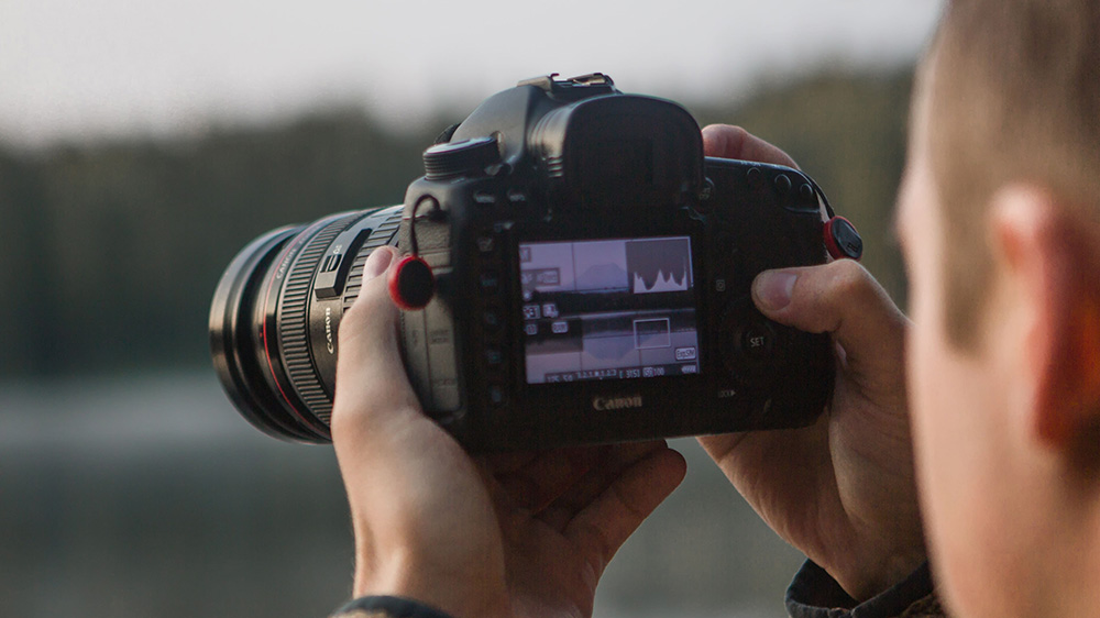A man holding a camera on which a histogram is displayed